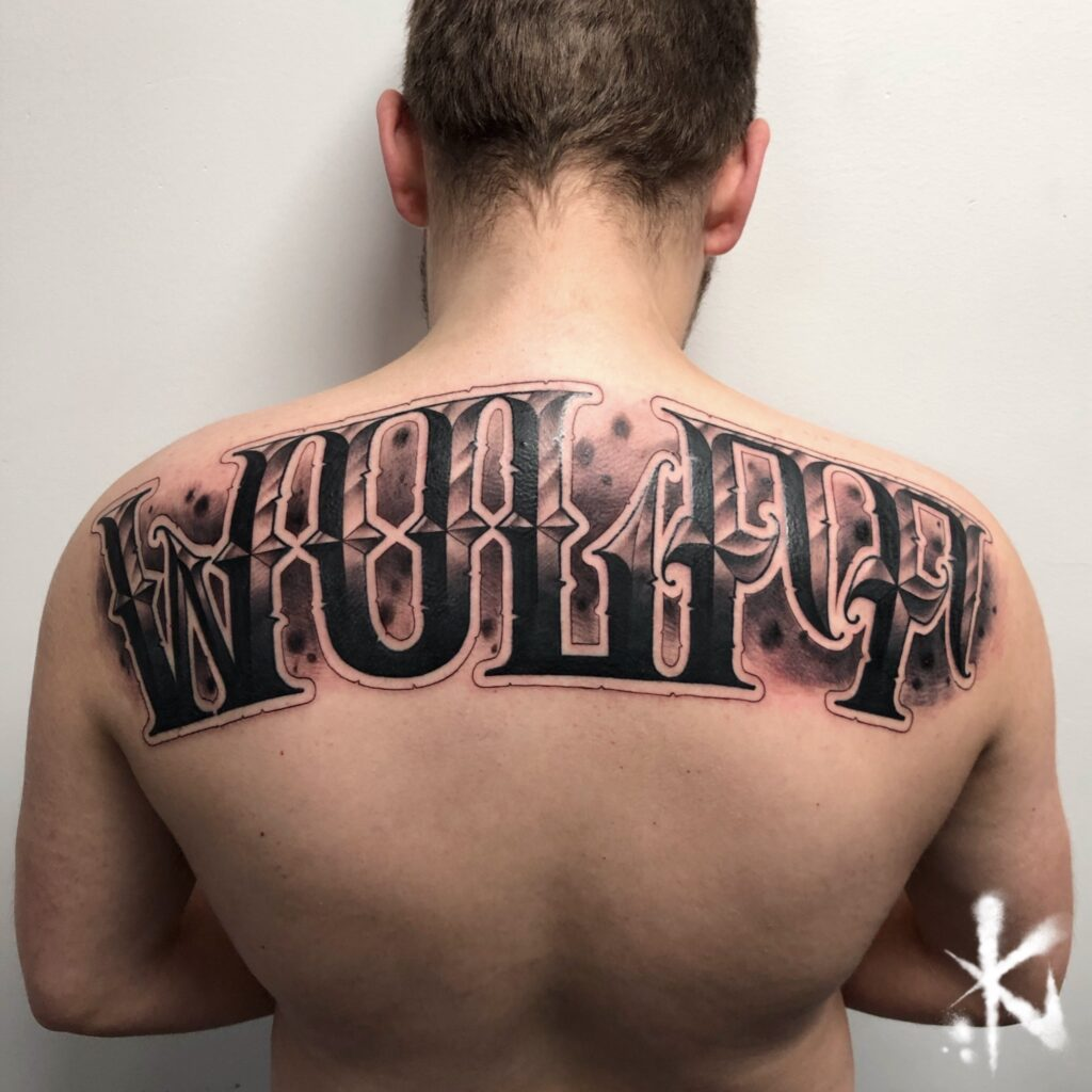 Upper back lettering tattoo